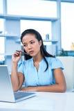 Rozważny młody bizneswomanu obsiadanie przy jej biurkiem Zdjęcia Stock