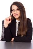 Rozważny młody bizneswomanu obsiadanie przy jej biurkiem trzyma pióro Obrazy Stock