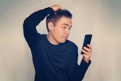 Rozważny młody człowiek czyta wiadomość na czarnym nowożytnym smartphone Nieszezególna emocja na jego twarzy Facet drapa jego kie Obraz Royalty Free