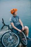rozważny młody próbny rowerzysta relaksuje na skalistej falezie obraz royalty free