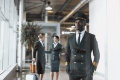 rozważny potomstwo pilot w lotnisku z stewardesami zdjęcie stock