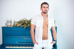 Rozważny, przystojny mężczyzna z brodą w biel ubraniach przeciw tłu pianino, rzępoląca koszula z nagą półpostacią Fotografia Stock