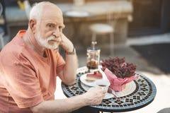 Rozważny starszy mężczyzna pije herbaciany samotnego fotografia stock