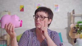 Rozważny w średnim wieku kobiety obsiadanie w żywym pokoju z prosiątko bankiem w jego ręce zbiory wideo