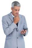 Rozważny biznesmen dotyka jego podbródek i patrzeje jego telefon Zdjęcia Royalty Free