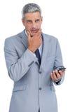 Rozważny biznesmen dotyka jego podbródka mienia telefon komórkowego Obrazy Stock