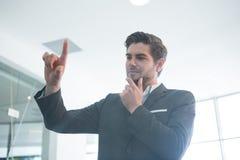 Rozważny biznesmen dotyka niewidzialnego cyfrowego ekran Obraz Royalty Free