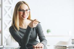 Rozważny bizneswoman wskazuje przy biurkiem Zdjęcia Stock