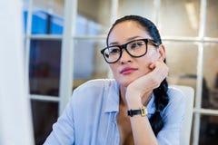 Rozważny bizneswomanu obsiadanie przy jej biurkiem Fotografia Royalty Free
