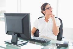 Rozważny bizneswomanu obsiadanie przy jej biurkiem patrzeje daleko od Zdjęcia Stock