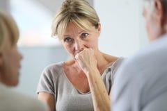 Rozważna starsza kobieta słucha grupy Zdjęcie Stock