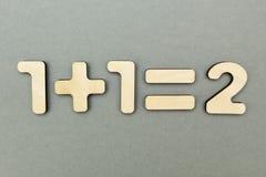 Rozwiązany przykład od drewnianych postaci: jeden plus jeden jest równy dwa fotografia royalty free