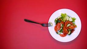 Rozwidla z plasterkiem ogórek na sałatkowym talerzu na różowym tle, żywność organiczna zdjęcie stock