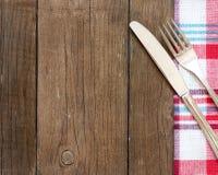 Rozwidlenie i nóż na kuchennym ręczniku i starym drewnianym stole Obrazy Stock