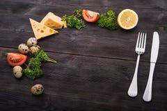 Rozwidlenie i nóż z pomidorem, ser, jajka Zdjęcia Stock