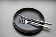 Rozwidlenie i nóż na czarnym talerzu Fotografia Royalty Free
