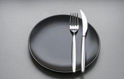 Rozwidlenie i nóż na czarnym talerzu Obraz Royalty Free
