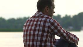 Rozwiedziony mężczyzny obsiadanie na brzeg rzekim myśleć o życie niesprawiedliwości, midlife kryzys zbiory