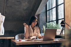 Rozwija projekt Skoncentrowana młoda kobieta pracuje używać lapt Obrazy Stock