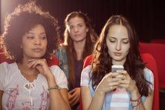 Rozzłościć kobieta texting podczas filmu Zdjęcie Royalty Free