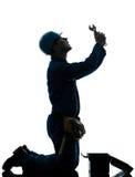 Réparez la silhouette de prière de désespoir d'ouvrier d'homme Images stock
