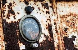 RPM gauge on an old rusty panel with chipping peeling paint flaking away. To the ground Stock Photography