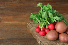 Rpotatoes  with radishes. Red potatoes on burlap with radishes on wooden brown background Stock Photo