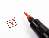 Rred pen with marked checkbox. Close-up shot of filled check box and red marker Royalty Free Stock Image