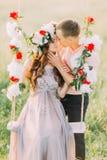 Rretty junges blondes tragendes lila Kleid und Kranz der Umfassung des gutaussehenden Mannes, die im Schwingen sitzt Stockbilder