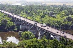 Rriver曲拱有许多移动的汽车的石头桥梁 库存照片