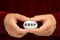 RRSP scritto su un uovo ha tenuto dall'uomo Fotografia Stock
