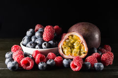Rspberry en bosbes met een passionfruit, op donkere achtergrond, Stock Afbeeldingen