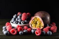 Rspberry et myrtille avec un passionfruit, sur le fond foncé, Images stock