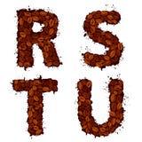 RSTU, Buchstaben des englischen Alphabetes, gemacht von den Kaffeebohnen, im Schmutz Lizenzfreie Stockbilder