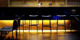 Rtbar räknare med stolar i tom comfoable restaurang på natten royaltyfria bilder