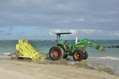 Râteau de ressac sur le tracteur par la mer Image stock
