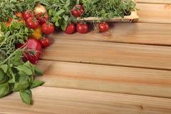 Örter och grönsaker på ett tomt träbräde Arkivfoto