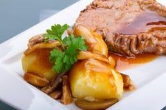Rôti de porc avec la sauce au jus et les pommes de terre Photographie stock libre de droits