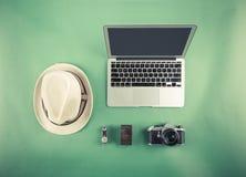 Rétro moquerie de hippie  Ordinateur portable, chapeau et vieil appareil-photo sur le fond vert Image filtrée Image libre de droits