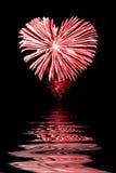 Rött fyrverkeri i formen av en hjärta, vatten Arkivfoto