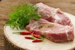 Rått griskött på skärbräda Arkivfoto