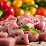 Rått griskött på skärbräda och nya grönsaker stänger sig upp Arkivfoton