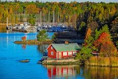 Rött hus på stenig kust av den Ruissalo ön, Finland Arkivbild