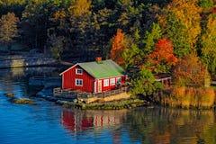 Rött hus på stenig kust av den Ruissalo ön, Finland Arkivfoton