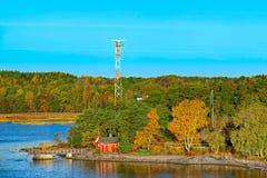 Rött hus på stenig kust av den Ruissalo ön, Finland Royaltyfria Bilder
