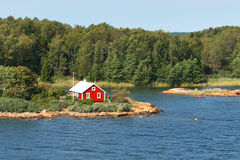 Rött hus på stenig kust av Östersjön Royaltyfri Bild