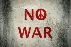 Rött inga krigmeddelande och grafitti för fredsymbol på grungecimentwa Royaltyfri Fotografi