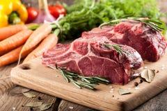 Rått nötköttkött på skärbräda och nya grönsaker Arkivfoto