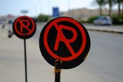 Rött och svärta inget parkeringstecken på vägen Arkivfoton