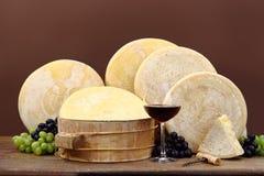 Rött vin med ost och druvor Royaltyfria Bilder